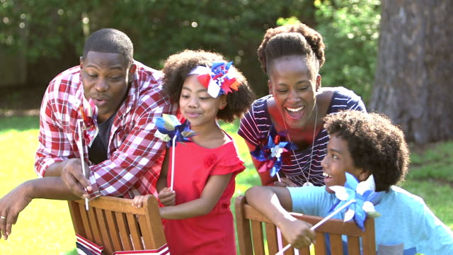 Black family, two children playing on American holiday A family of four having fun outdoors on the fourth of july or memorial day. They are playing with red, white and blue pinwheels. The little girl, 7 years old, has a patriotic bow in her hair. family 4th of july stock videos & royalty-free footage
