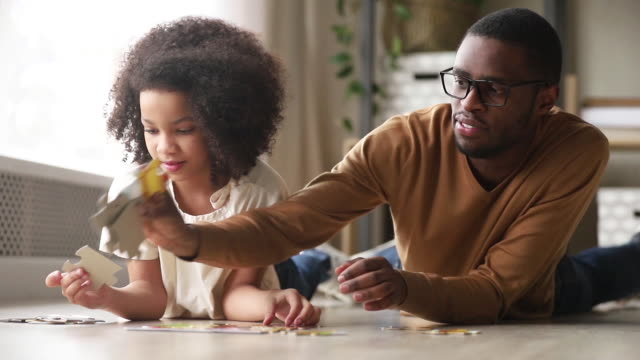 Black father and daughter collect jigsaw puzzle lying on floor