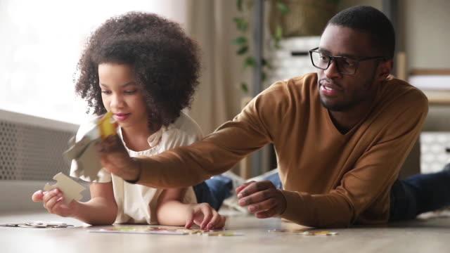 vidéos et rushes de le père et la fille noirs recueillent le puzzle se trouvant sur l'étage - vue partielle