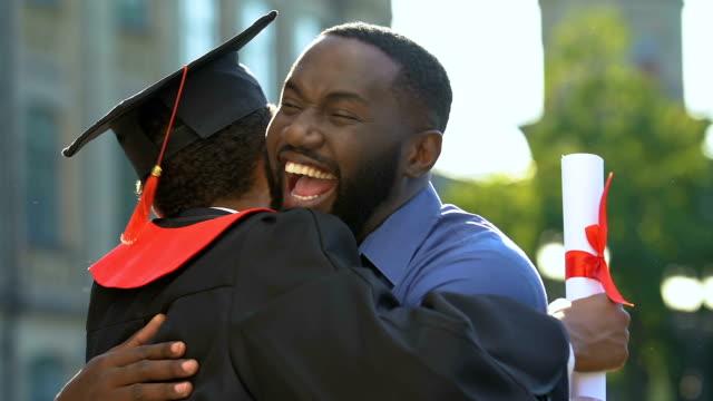black father and son hugging in university campus after graduation ceremony - celebrazione della laurea video stock e b–roll