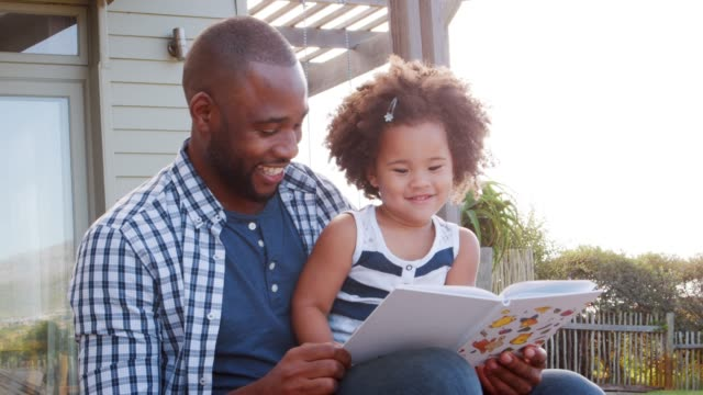 vídeos de stock e filmes b-roll de black father and young daughter reading a book outdoors - mãe solteira