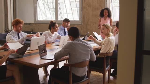 会議でチームにドキュメントを説明する女性の黒の上司 - ミーティング点の映像素材/bロール