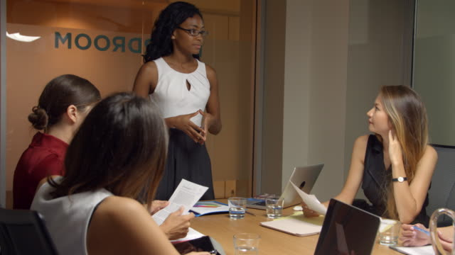 Black female boss stands to address team at business meeting video