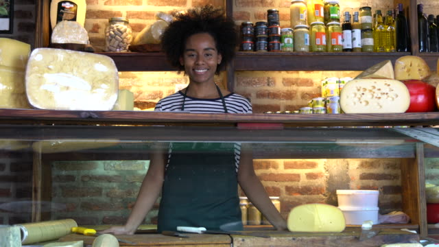 Black female business owner of a deli standing behind the refrigerator smiling at camera Black female business owner of a deli standing behind the refrigerator smiling at camera very cheerfully homegrown produce stock videos & royalty-free footage
