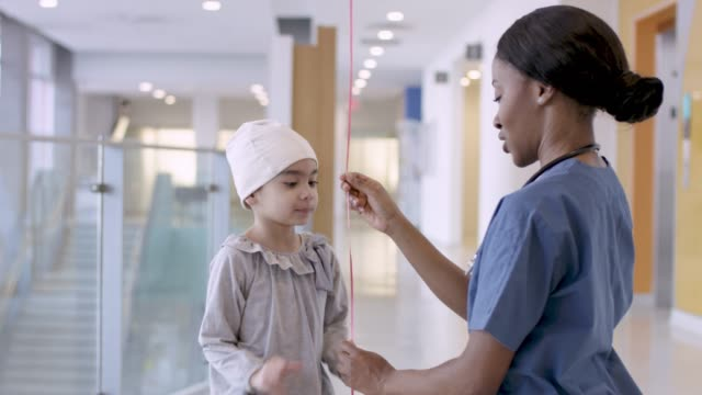 Black Female Nurse Giving Balloon To Child Cancer Patient video