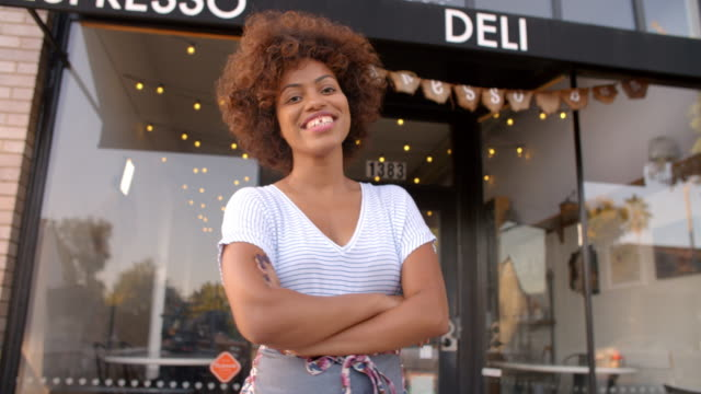 Black female owner walks into focal plane outside coffee shop - video