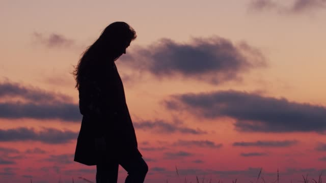 Black female silhouette standing in profile on colorful evening sky background