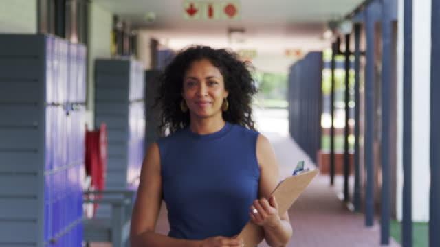 Black female teacher walks into focus in school corridor