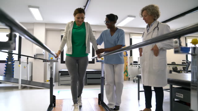 vídeos de stock e filmes b-roll de black female therapist motivating female patient walk with the help of parallel bars and senior orthopedist observing next to them - esforço