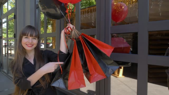 black Friday, girl after shopping with balloons shows of finger on bags with purchases