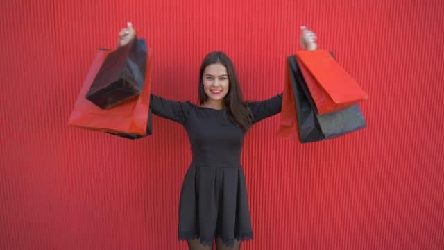 vídeos y material grabado en eventos de stock de viernes negro, retrato de niña feliz al cliente con las compras en bolsas de compras durante la temporada de ventas - black friday sale