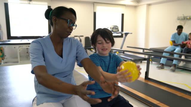 schwarz freundliche therapeut erklärt die übung zu kleinen jungen, während er ihr mit einem ball in der physiotherapie folgt - physiotherapeut stock-videos und b-roll-filmmaterial