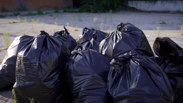 stockvideo's en b-roll-footage met zwarte vuilniszakken zijn gemaakt op hun plaats. een vuilniswagen komt binnenkort aan en neemt de vuilnis - tas