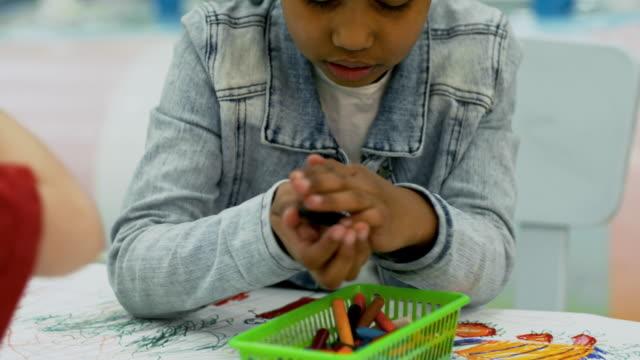 black girl choosing colors for picture - matita colorata video stock e b–roll