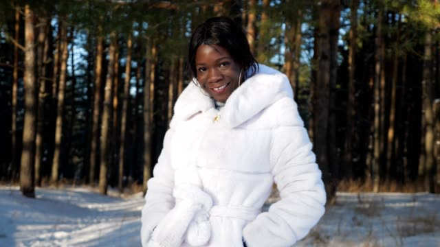 black girl poses holding hands in pockets against snowy park