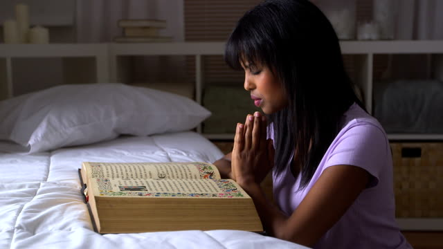 Black girl praying with Bible on bed video