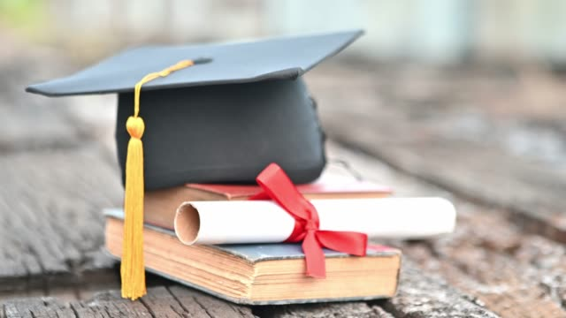 black graduates hat and yellow tassels pasted on old wood - tocco accademico video stock e b–roll