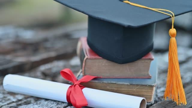 black graduates hat and yellow tassels pasted on old wood - celebrazione della laurea video stock e b–roll