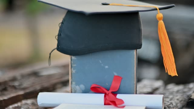 Black graduates hat and yellow tassels pasted on old wood