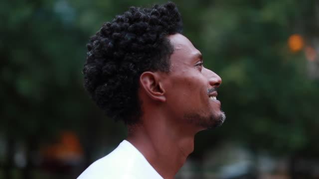 vidéos et rushes de type noir restant dehors dans la nature regardant le ciel, tournant autour de l'homme africain de 360 degrés restant - 30 34 ans