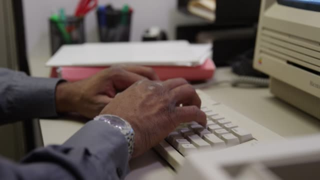 Black hands type on keyboard then tilt to old Macintosh Classic computer Old technology in office space. Black hands type on keyboard then tilt to old Macintosh Classic computer. High quality 4k footage 20th century stock videos & royalty-free footage