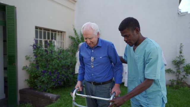 vidéos et rushes de travailleur de santé noir aidant l'homme aîné avec le marcheur de mobilité extérieur - infirmier