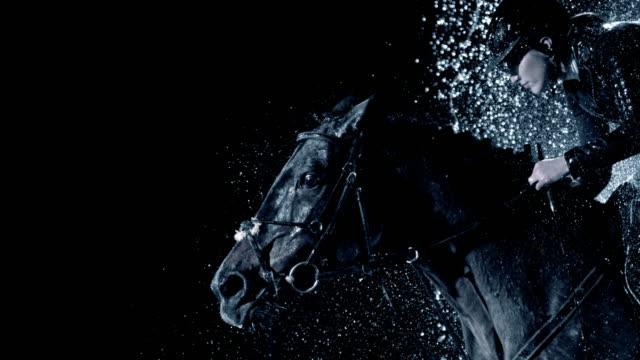 slo mo svart häst som hoppar genom ett vattenfall med en kvinnlig ryttare - hästhoppning bildbanksvideor och videomaterial från bakom kulisserna