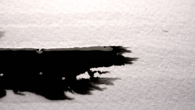 Black ink run and bleeding in white paper. Ideal ink texture to add to modern projects video