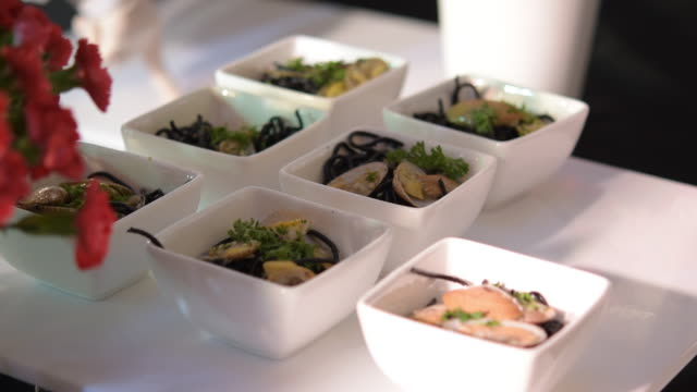 Black ink spaghetti in small bowls arrange in row for serving in party