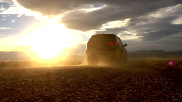 slow motion: black jeep driving on dusty gravel road towards mountains at sunset - close up auto video stock e b–roll