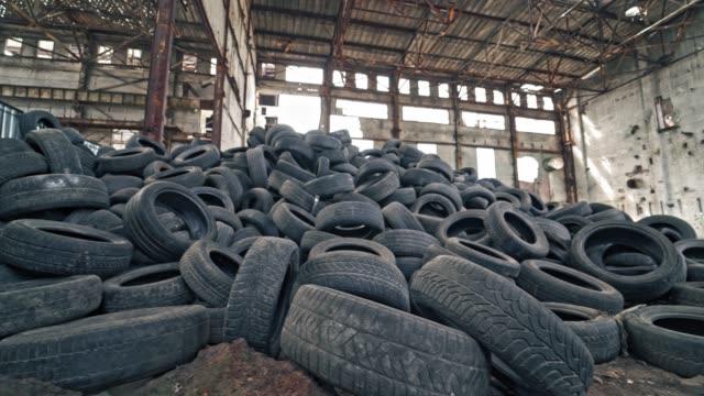 古い放棄された建物の床に横たわっている黒いジャンクタイヤ。 - 積み重なる点の映像素材/bロール