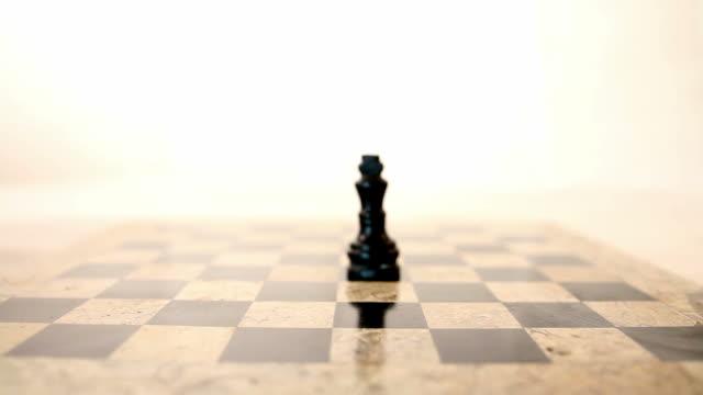 ein schwarzer könig steht in der mitte ein schachbrett und eine person legt einen weißen könig vor den schwarzen könig - könig schachfigur stock-videos und b-roll-filmmaterial