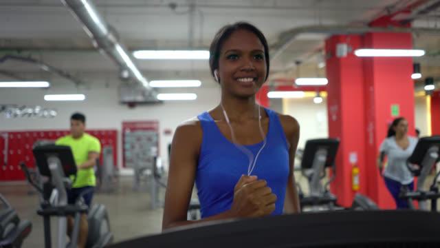 siyah latin amerikalı kadın koşu bandı üzerinde çalışan spor salonunda - kulaklık seti ses ekipmanı stok videoları ve detay görüntü çekimi