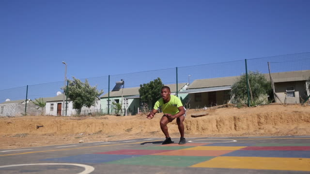 Black male doing some exercises outside A black male does some burpees as part of his training regime outside on a court, Kayamandi South Africa sportsperson stock videos & royalty-free footage