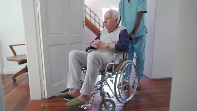 Black male nurse pushing senior patient in wheelchair Black young male nurse pushing senior male patient in wheelchair in nursing home pushing wheelchair stock videos & royalty-free footage