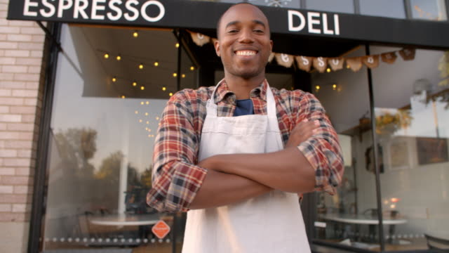 Black male owner walks into focal plane outside coffee shop video
