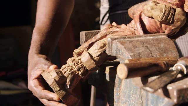 Black man at work, artist working, art, wood, statue video