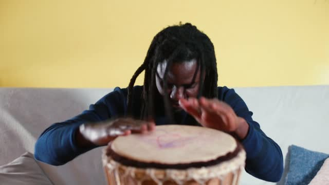 Black man bangs drum home in self-isolation with his hands. Relaxation psyche.