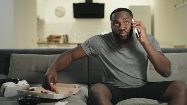 vídeos de stock e filmes b-roll de black man eating pizza in front of tv. male fan commenting match results - pizza