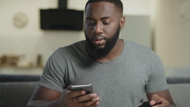 Black man holding phone at open kitchen. Concentrated guy texting in smartphone. Black man holding phone in hand at open kitchen. Concentrated guy texting in smartphone. Surprised male person looking at mobile phone at kitchen. Black male person getting news by cellphone. face to face stock videos & royalty-free footage