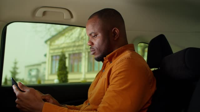 Black man in car backseat networking on tablet pc