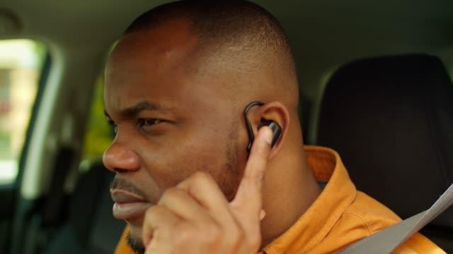 Black man in car talking using hands-free device