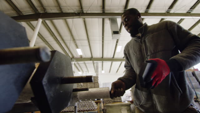 a black man in his twenties with a beard rotates and tightens a black end cap in a manufacturing facility - затягивание стоковые видео и кадры b-roll