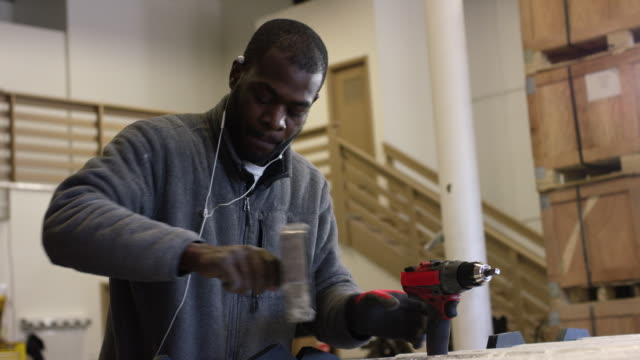 A Black Man in His Twenties with a Beard Rotates and Tightens a Black End Cap in a Manufacturing Facility with a Power Drill in the Foreground A Black Man in His Twenties with a Beard Rotates and Tightens a Black End Cap in a Manufacturing Facility with a Power Drill in the Foreground manufacturing occupation stock videos & royalty-free footage