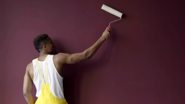 Black man in yellow costume African American holding paint roller in hand paints the wall in purple color.