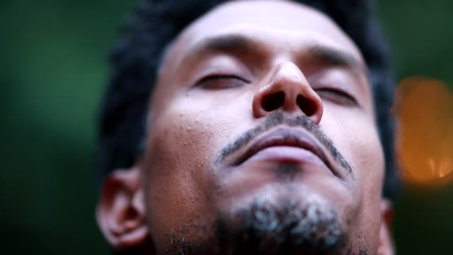 Black man meditating outside taking a deep breath and opening eyes to the sky, person contemplating life Black man meditating outside taking a deep breath and opening eyes to the sky, person contemplating life mental wellbeing stock videos & royalty-free footage