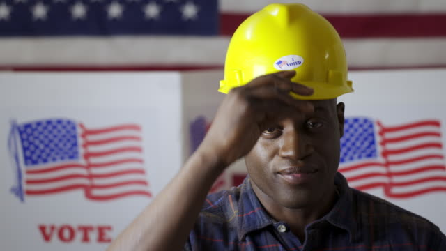 Black man puts on hard hat with