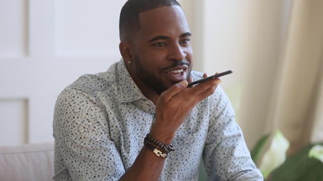 vídeos de stock e filmes b-roll de black man speak to virtual voice recognition assistant on smartphone - mensagem
