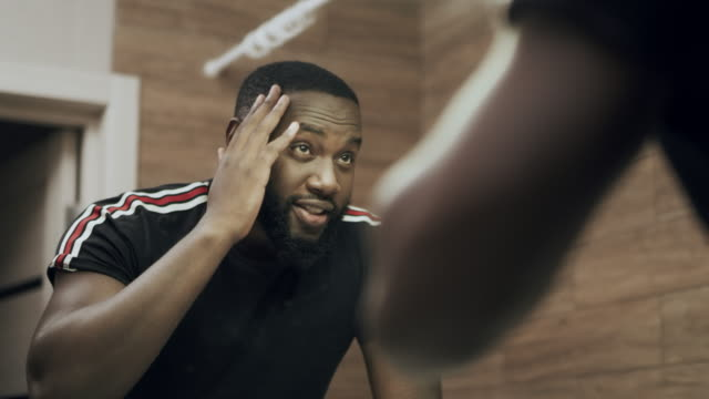 Black man standing in front of mirror at bathroom. Portrait of smiling man.