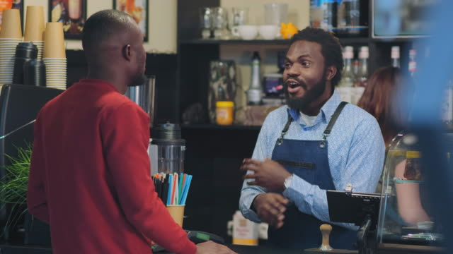 black man stands behind bar counter and talks Afro-American bearded man in apron stands behind bar counter and talks with client from native country in cafe bartender stock videos & royalty-free footage
